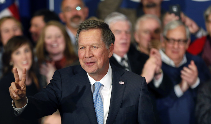 Republican presidential candidate Ohio Gov. John Kasich arrive to a cheering crowd Tuesday, Feb. 9, 2016, in Concord, N.H., at their primary night campaign rally. (AP Photo/Jim Cole)