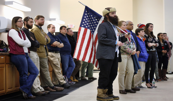 Rod Webber of Boston, holds an American flag while attending a town hall-style campaign event held by Republican presidential candidate, Sen. Ted Cruz, R-Texas, Monday, Feb. 8, 2016, in Barrington, N.H. (AP Photo/Robert F. Bukaty)