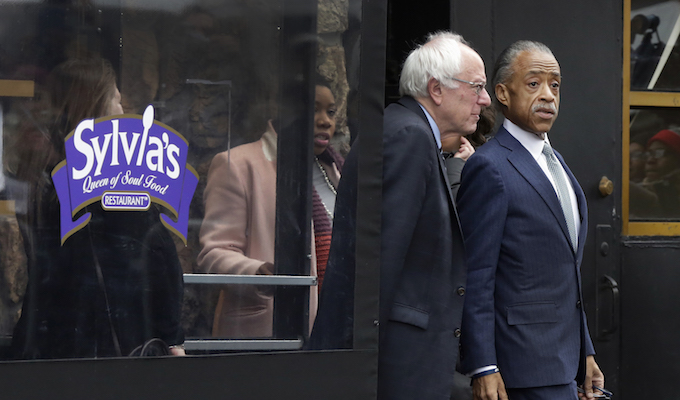 The Rev. Al Sharpton  escorts Democratic presidential candidate Sen. Bernie Sanders, I-Vt. as they leave a breakfast meeting at Sylvia's Restaurant, Wednesday, Feb. 10, 2016, in the Harlem neighborhood of New York. Sanders defeated former Secretary of State Hillary Clinton on Tuesday in the New Hampshire primary. (AP Photo/Richard Drew)