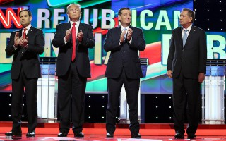 Republican presidential candidates, Sen. Marco Rubio, R-Fla, from left, Donald Trump, Sen. Ted Cruz, R-Texas, and Ohio Gov. John Kasich stand up for the national anthem during a presidential debate at the University of Miami in Coral Gables, a suburb of Miami on Thursday, March 10, 2016. (Pedro Portal/The Miami Herald via AP) MANDATORY CREDIT