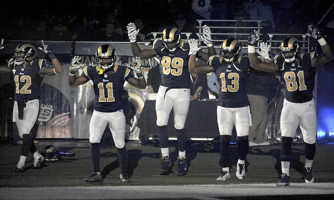 "FILE - In this Nov. 30, 2014, file photo, St. Louis Rams players, from left, Stedman Bailey (12), Tavon Austin (11), Jared Cook, (89) Chris Givens (13) and Kenny Britt (81) raise their arms in awareness of the events in Ferguson, Mo., as they walk onto the field during introductions before an NFL football game against the Oakland Raiders in St. Louis. The players said after the game, they raised their arms in a ""hands up"" gesture to acknowledge the events in Ferguson. (AP Photo/L.G. Patterson, File)"