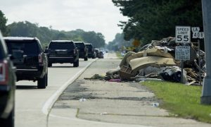 The motorcade of Republican presidential candidate Donald Trump passes piles of rubbish on the side of the road in East Baton Rouge, La., Friday, Aug. 19, 2016. (AP Photo/Max Becherer)