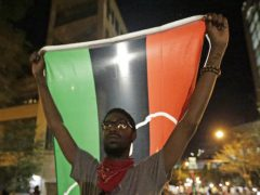 A protester holds a flag as he marches in the streets of Charlotte, N.C. Friday, Sept. 23, 2016 over Tuesday's fatal police shooting of Keith Lamont Scott. (AP Photo/Chuck Burton)
