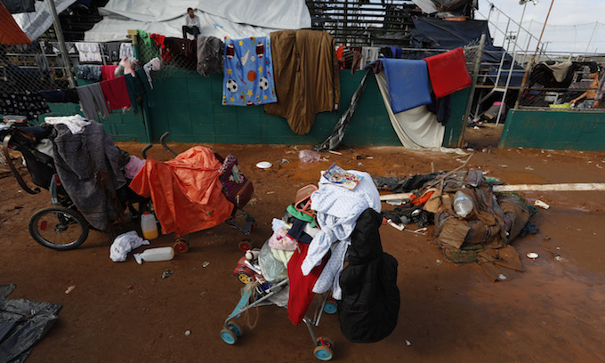 With food and bathrooms cut off, migrants begin exodus to distant shelter