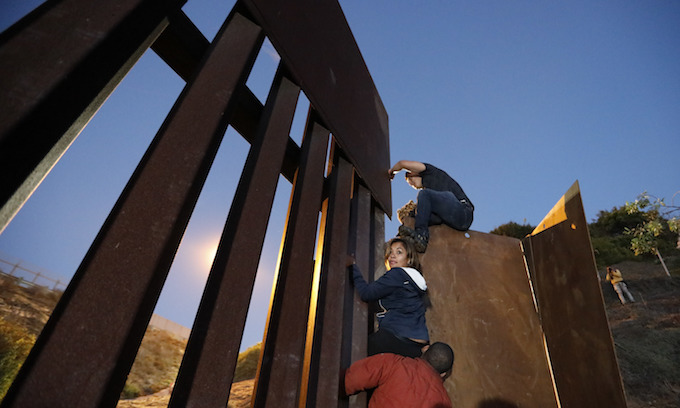 Central Americans moved from border, others scale wall into US