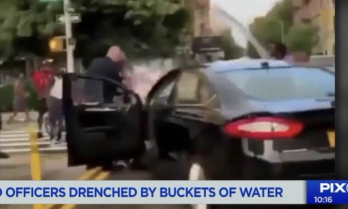 Groups of jeering men douse NYPD cops with water
