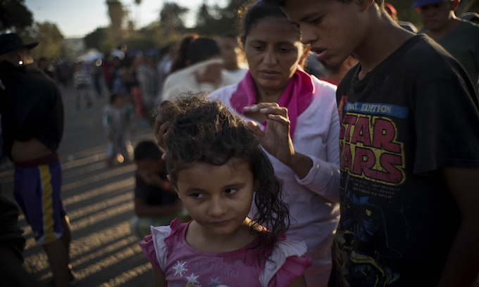 Subdued Central Americans at Tijuana border camp mull options